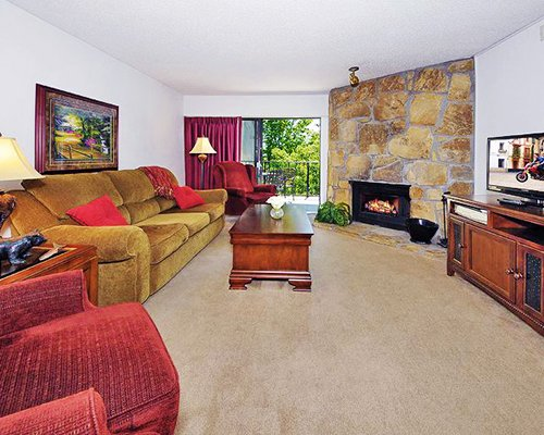 A well furnished living room with a television sofas fire at the fireplace and an outside view.