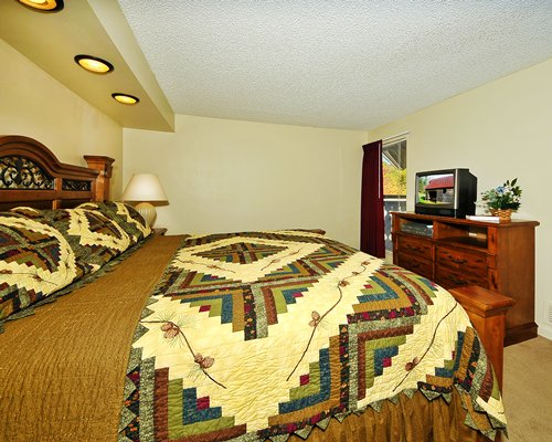 A well furnished bedroom with queen bed television and balcony.