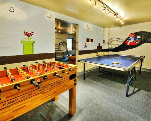 An indoor recreation room with pool and air hockey table.