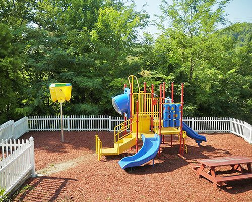 Outdoor kids playground alongside wooded area.