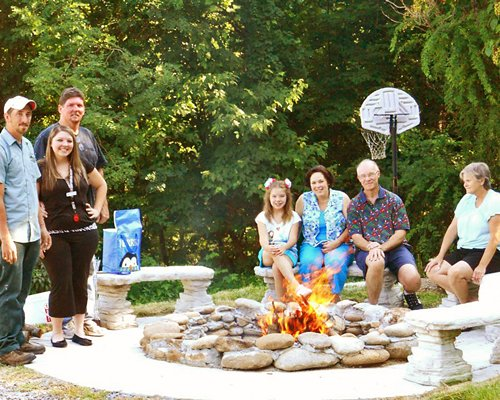 People on a picnic area with campfire and basketball net alongside the wooded area.