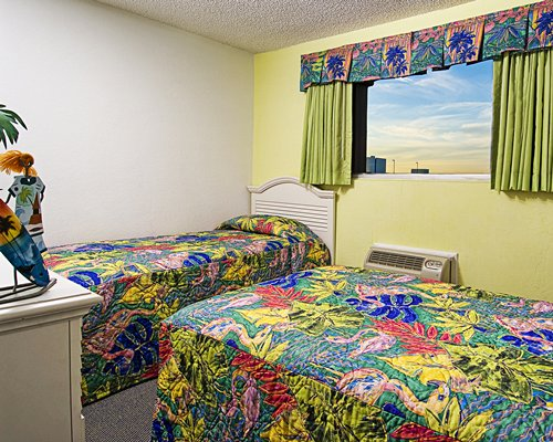 A well furnished bedroom with two beds and an outside view.