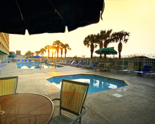 Outdoor swimming pool with hot tub dining chaise lounge chairs sunshades and palm trees.