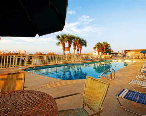 Outdoor swimming pool with chaise lounge chairs patio furniture and palm trees.