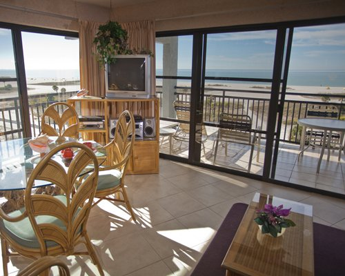 A well furnished living room with television dining area balcony patio chairs and ocean view.