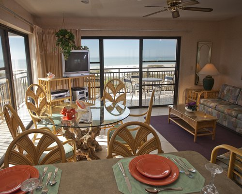 A well furnished living room with a television dining area balcony and beach view.