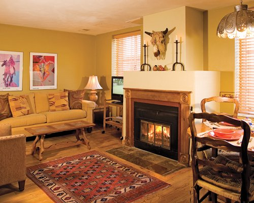 A well furnished living area with a television fire at the fireplace alongside a dining area.