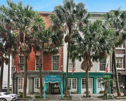 Scenic exterior view and entrance of Hotel de L'eau Vive/Maison Orleans with palm trees.