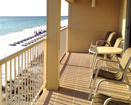 A balcony with patio furniture facing the beach.