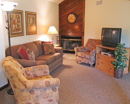 A well furnished living room with a pull out sofa and a fireplace.