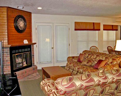 A well furnished living room with a double pull out sofa television and a fireplace.