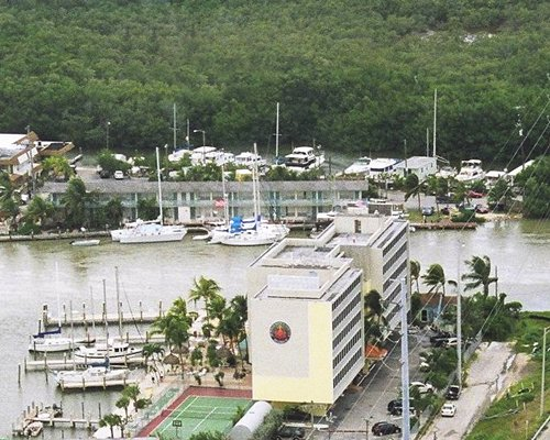 An aerial view of multi story resort unit alongside waterfront with marina.