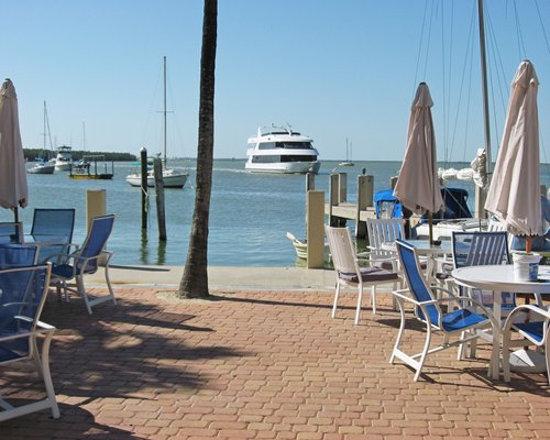 An outdoor dining area with boats and a pier.