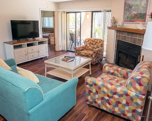 A well furnished living room with a television fireplace and patio.