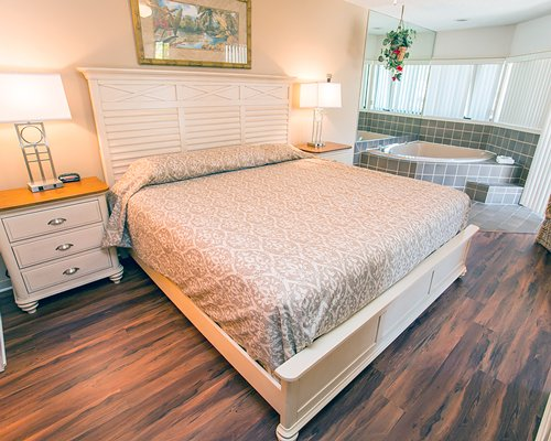 A well furnished bedroom with queen bed alongside a hot tub.