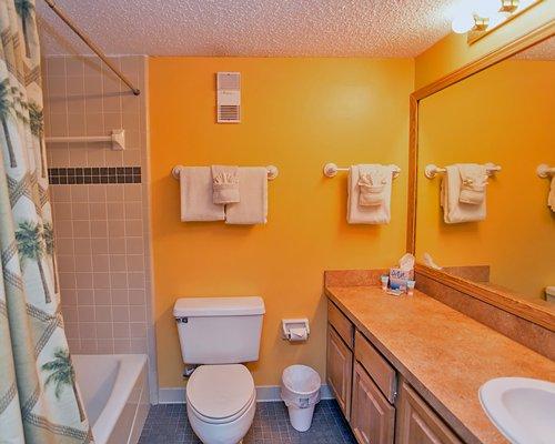 A bathroom with a bathtub and a single sink vanity.