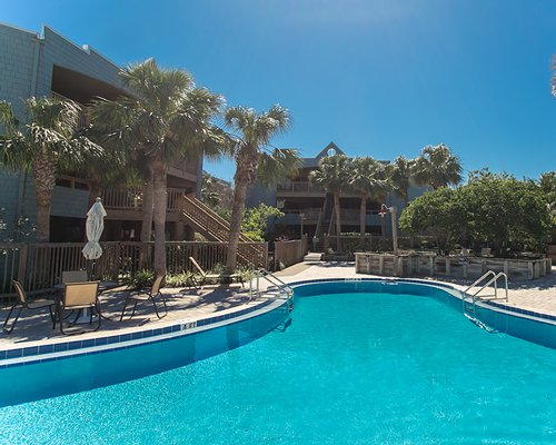 An outdoor swimming pool with patio furniture alongside the resort.