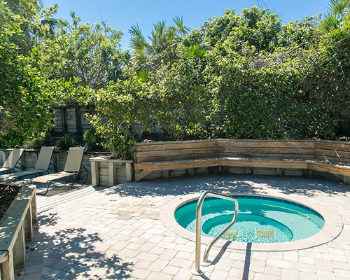 Outdoor hot tub with chaise lounge chairs.