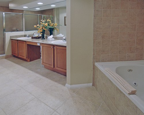 A bathroom with double sink vanity and bathtub.
