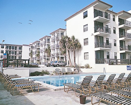 An outdoor swimming pool with chaise lounge chairs alongside multi story units with private balconies.
