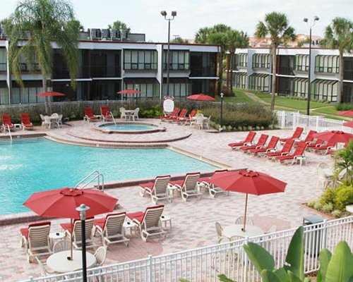 An outdoor swimming pool with patio furniture sunshades and chaise lounge chairs alongside the resort units.