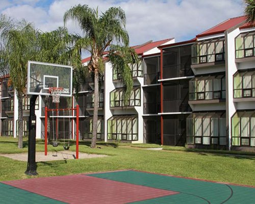 An outdoor basketball court alongside a resort units.