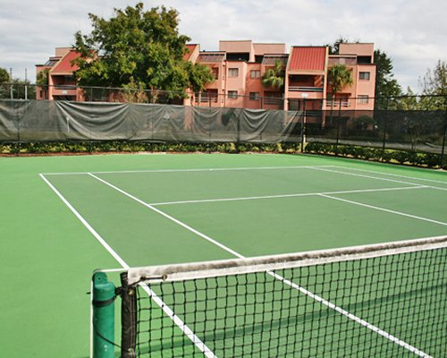 An outdoor tennis court alongside resort units.