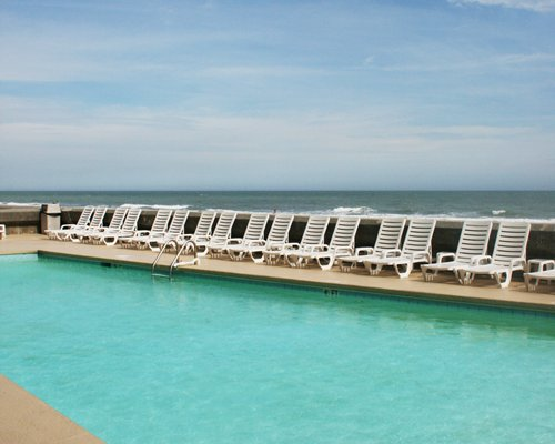 An outdoor swimming pool with chaise lounge chairs alongside the ocean.