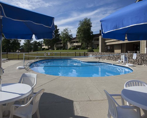 An outdoor swimming pool with patio furniture alongside resort units.