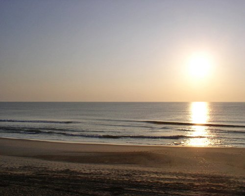 View of the beach and ocean during sunset.
