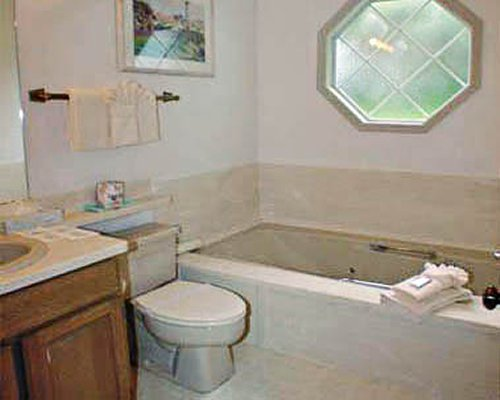 A bathroom with bathtub and single sink vanity.