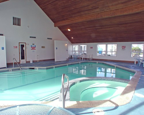 An indoor swimming pool with a hot tub and patio furniture.