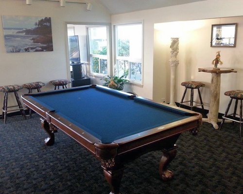 An indoor recreational room with a pool table and outside view.