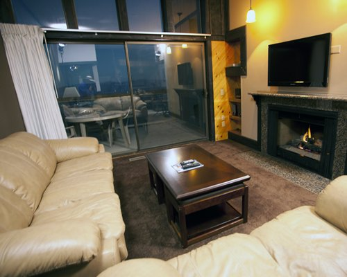 A well furnished living room with a television fire in the fireplace and an outside view.