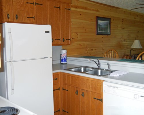 A kitchen with a refrigerator and double sink.