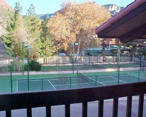 Balcony view of an outdoor tennis court.
