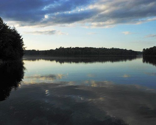 View of the lake surrounded by wooded area.