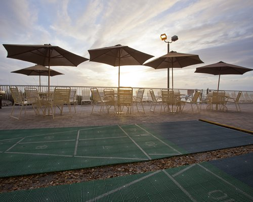 A view of shuffleboard with patio furniture and sunshade at dusk.