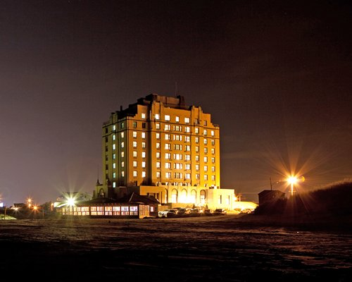 Exterior view of Legacy Vacation Club Brigantine Beach resort at night.