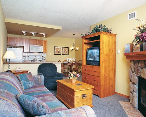A well furnished living room with a television and fireplace alongside kitchen.