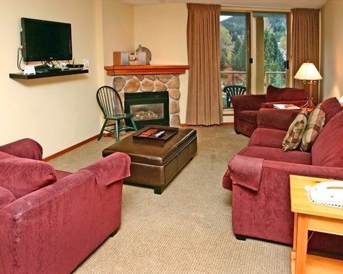 A well furnished living room with television fireplace and balcony.