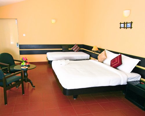 A well furnished bedroom with double beds and patio furniture.