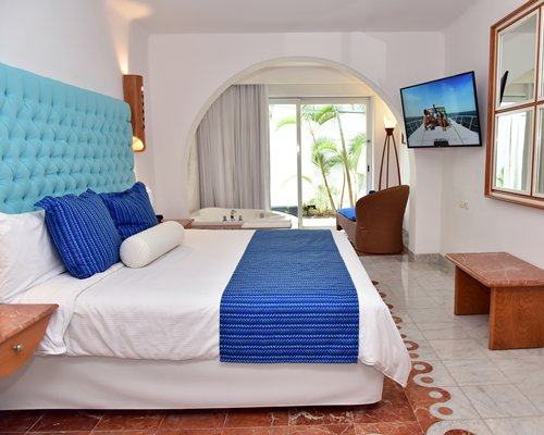 A well furnished bedroom with a king bed bathtub and outdoor view.