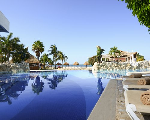 Large outdoor swimming pool with chaise lounge chairs thatched sunshades and palm trees alongside the ocean.