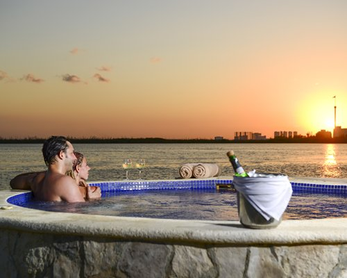 A couple in a hot tub alongside the beach at dusk.