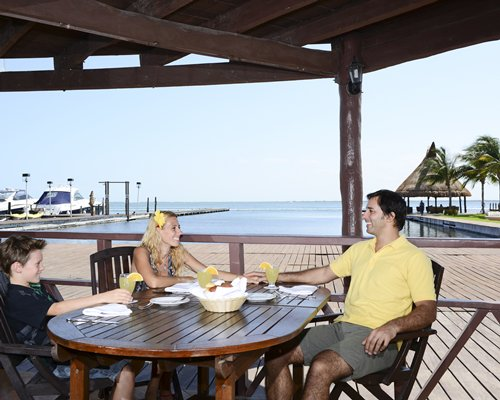 A family at an outdoor dining table alongside the wooden pier and boats.