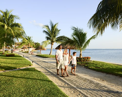 A family walking in a landscaped pathway alongside the beach.
