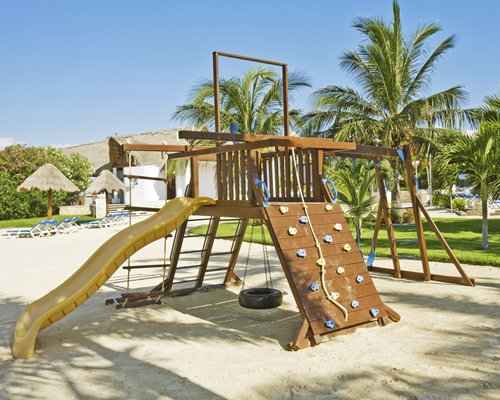 Playground with kids playscape alongside chaise lounge chairs and thatched sunshades.
