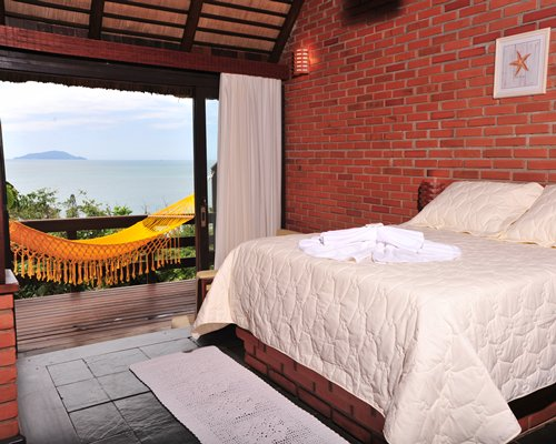 A well furnished bedroom with hammock at the balcony and outside view.