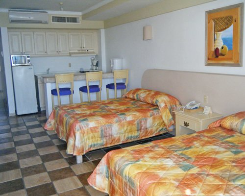 A well furnished bedroom with two king beds open plan kitchen and breakfast bar.